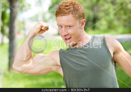 Muscular man showing his biceps stock photo, Young muscular man showing his biceps against blur background by Tyler Olson