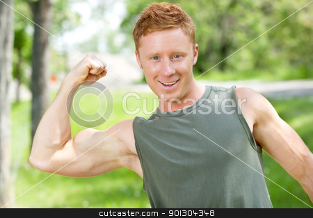 Athletic man showing muscles stock photo, Portrait of athletic man showing muscles outdoors by Tyler Olson