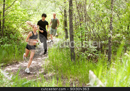 Friends running in the forest stock photo, Three friends running in the forest on pathway by Tyler Olson