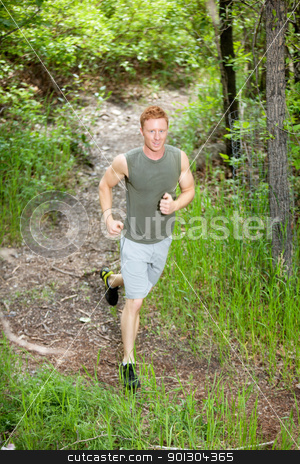 Handsome man jogging stock photo, Portrait of handsome man running in forest against blur background by Tyler Olson