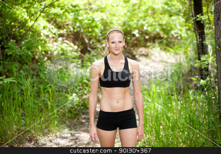 Portrait of woman standing stock photo, Portrait of a beautiful woman standing in sportswear against blur background by Tyler Olson