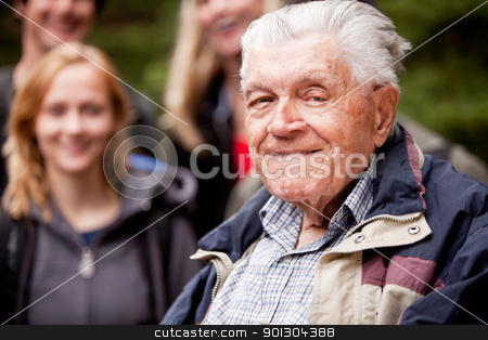 Elderly Man Outdoors stock photo, A portrait of an elderly man with young people in the background by Tyler Olson