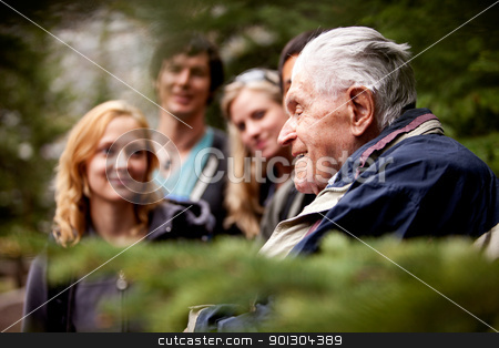 Elderly Man Group  stock photo, An elderly man telling stories to a group of young people by Tyler Olson
