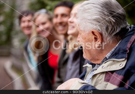 Elderly Guide stock photo, An elderly man guiding a group of young people in the forest by Tyler Olson