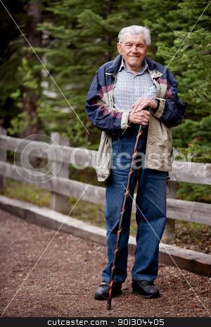 Senior Man Walking stock photo, A senior man walking outdoors on a path by Tyler Olson