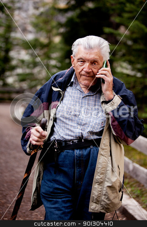 Senior on Cell Phone stock photo, A senior talking on a cell phone outdoors in the forest by Tyler Olson