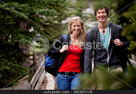 Hike Man Woman stock photo, A man and woman on a hike in the forest, smiling at the camera by Tyler Olson