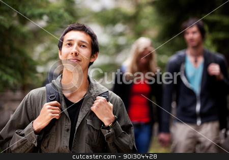 Camping Man stock photo, A man backpack camping in the forest with a group of friends in the background by Tyler Olson