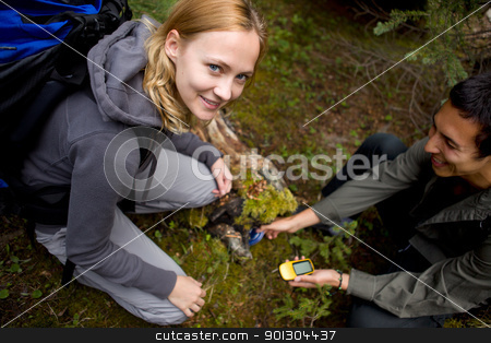 Geocaching stock photo, A young man and woman finding a geocache hidden in the forest by Tyler Olson