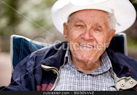 Happy Elderly Man stock photo, A portrait of a happy smiling elderly man sitting outdoors by Tyler Olson