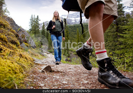 Woman on Mountain Hike stock photo, A happy woman on a mountain trail with mountains in the background by Tyler Olson