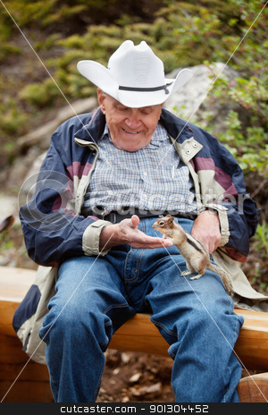 Elderly man playing with squirrel stock photo, Happy relaxed senior man playing with squirrel - focus on squirrel by Tyler Olson