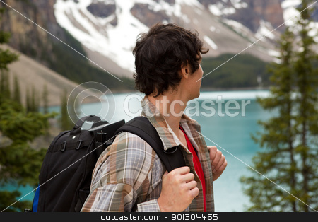 Man Looking at Mountain Lanscape stock photo, A young man looking out on a beautiful lake and mountain landscape by Tyler Olson