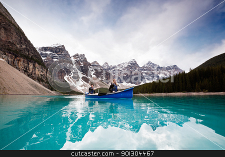 Scenic shot of couple sailing on calm water stock photo, Man and woman sailing on peaceful lake against mountain range by Tyler Olson