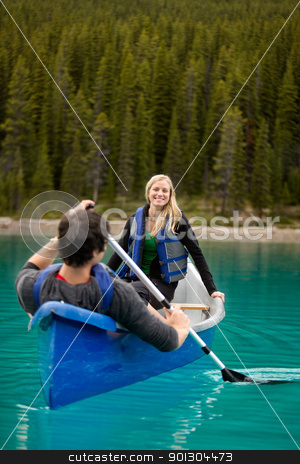 Canoe Couple stock photo, A happy couple canoeing on a glacial lake by Tyler Olson