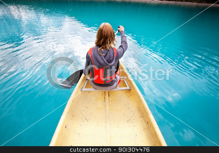 Woman rowing boat stock photo, Rear view of woman rowing boat on calm water by Tyler Olson