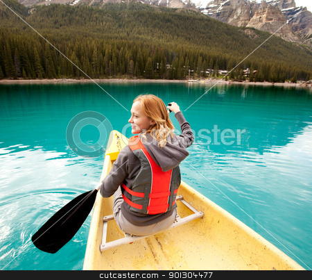 Canoe Woman Detail stock photo, A happy woman in a canoe on a clear glacial lake by Tyler Olson