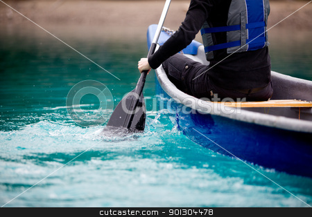 Canoe Paddle Detail stock photo, A person paddling a canoe in a turquoise galcier water by Tyler Olson