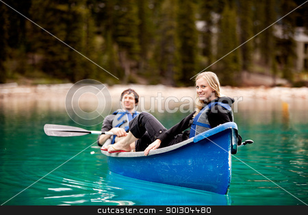 Couple Relaxing in a Canoe stock photo, A happy couple relaxing in a canoe on a glacial lake by Tyler Olson