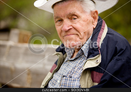 Senior Man Portrait stock photo, A portrait of a happy senior man on a bench by Tyler Olson