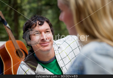 Outdoor Couple with Guitar stock photo, A man smiling at a woman with a guitar in the background by Tyler Olson