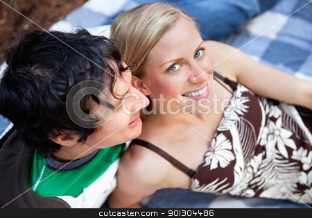 Young couple relaxing on picnic blanket stock photo, Top view close-up of young man and woman relaxing on picnic blanket by Tyler Olson