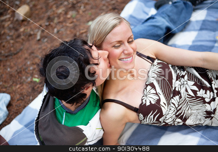 Romantic young guy kissing happy female stock photo, Top view of romantic young guy kissing happy female while on picnic by Tyler Olson