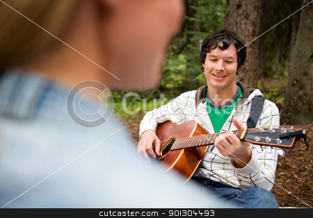 Man Playing Guitar for Woman stock photo, A man playing a guitar and singing for a woman by Tyler Olson