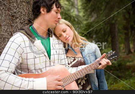 Man Playing Guitar Outdoor stock photo, A man playing a guitar outdoors for a woman by Tyler Olson