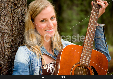 Woman with Guitar stock photo, A portrait of a woman holding a guitar in an outdoor setting by Tyler Olson
