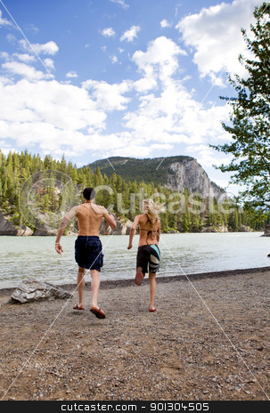 Man Woman Run Towards Water stock photo, A man and woman running towards the water on a hot summer day by Tyler Olson