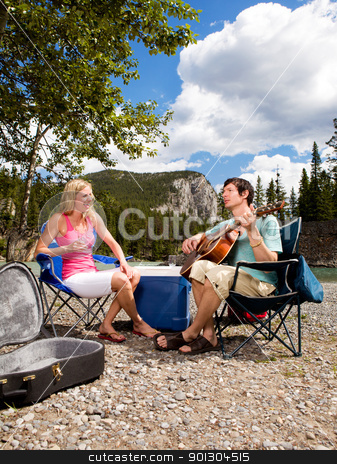 Camping Couple with Guitar stock photo, A happy couple with a guitar outdoors having fun by Tyler Olson