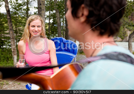 Outdoor Guitar stock photo, A man playing a guitar outdoors for a girl by Tyler Olson