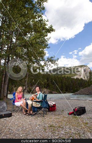 Camping Guitar Outdoor stock photo, A couple on a camping trip playing the guitar and relaxing by Tyler Olson