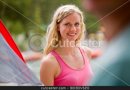 Outdoor Portrait Woman stock photo, A portrait of a woman outdoors setting up a tent. by Tyler Olson