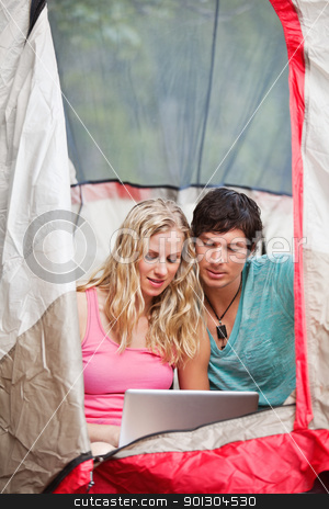 Couple working on laptop while camping stock photo, Young couple using laptop in tent while camping by Tyler Olson