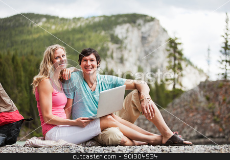 Relaxed couple with laptop while camping stock photo, Portrait of happy relaxed young couple with laptop while camping by Tyler Olson