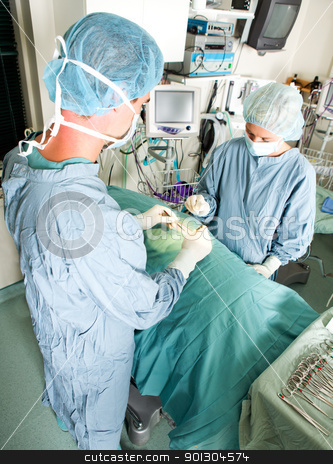 Live Surgery stock photo, A team doing surgery in a small operating room by Tyler Olson