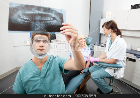 Dental Clinic stock photo, Radiodentist checking x-ray with assistant and patient having conversation in the background by Tyler Olson