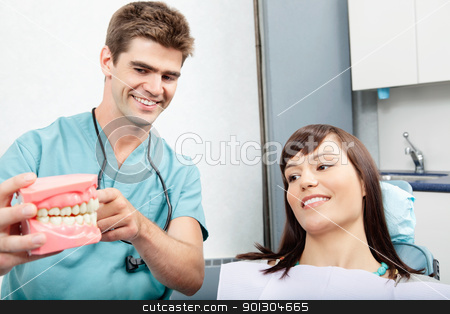 Dental Clinic Patient stock photo, Male dentist explaining a female patient denture work in dental clinic by Tyler Olson