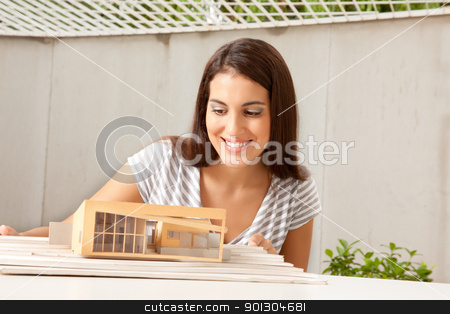 Architect with Model House stock photo, A female architect looking at a model house by Tyler Olson