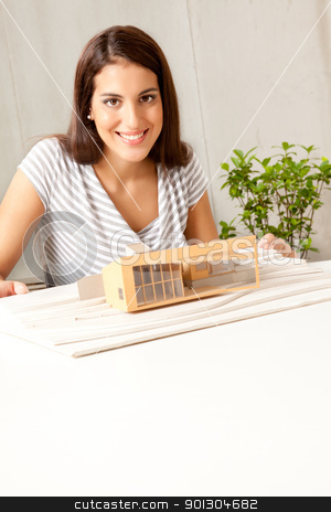 Young Architect stock photo, A young female architect smiling at the camera with a house model by Tyler Olson