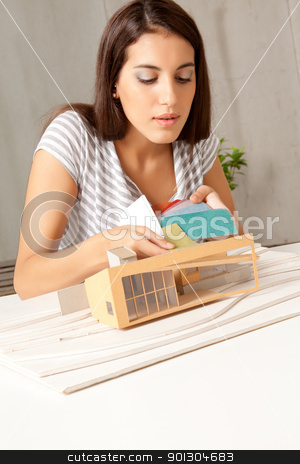 Color Swatch Model House stock photo, A young architect testing color swatching on a model house by Tyler Olson