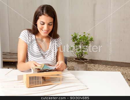 Architect with Model and Color Swatches stock photo, A young female architect looking at color swatches with a model house by Tyler Olson
