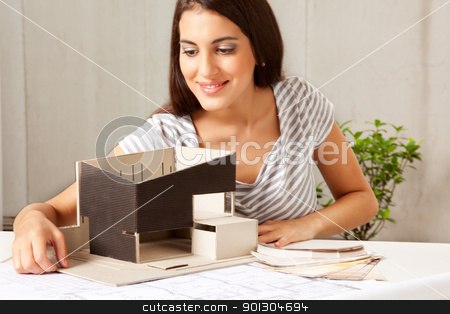 Architect with Blue Prints and Model stock photo, A female architect looking over a model house with blueprints and color swatches on the table by Tyler Olson