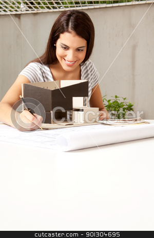 Architect stock photo, A young female architect working on a model and blueprints by Tyler Olson
