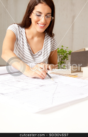 Female Architect with Blueprints stock photo, A female architect looking blueprints in an office by Tyler Olson