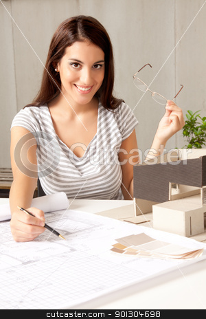 Architect with Blueprints and House Model stock photo, A young female architect at a desk with blueprints and model house by Tyler Olson