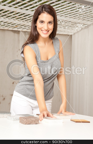 Designer with Floor Tiles stock photo, A female designer looking at the camera comparing floor tile swatches by Tyler Olson