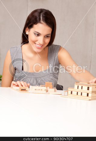 Architect Design stock photo, A female architect looking at a rough building model by Tyler Olson